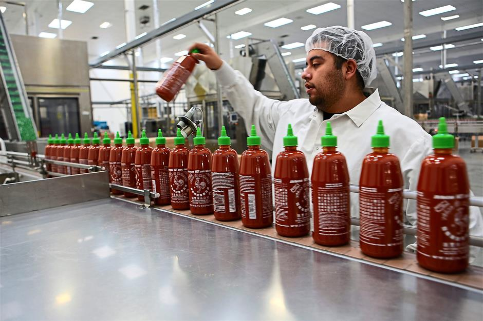 A worker keeping an eye on the production line as freshly filled Sriracha sauce bottles move on a conveyor for packaging at Huy Fong Foods in Irwindale, California.
