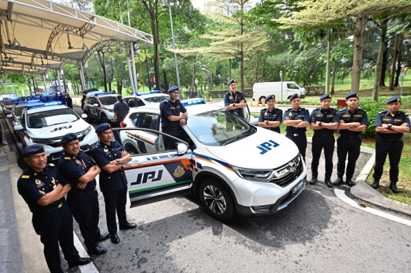 Brand new wheels:  JPJ officers standing  with their  new Honda  CRVs at the  handing over ceremony in  Petaling Jaya.