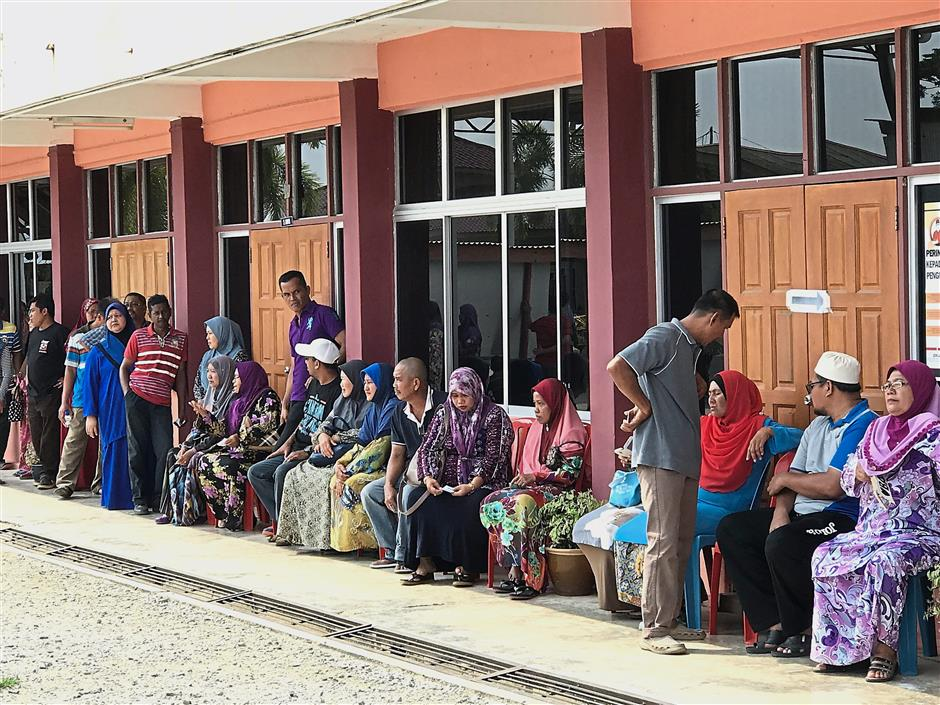 Elderly voters taking a seat while waiting in queue to vote at SK Sungai Burong in Tanjong Karang.