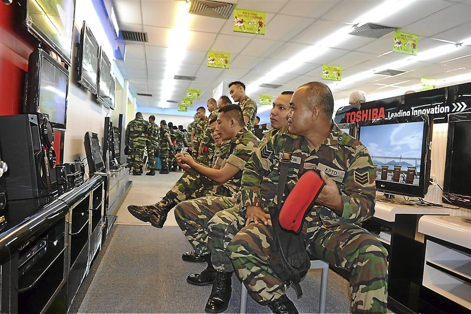 Soldiers are looking at electronical devices at a Pernama Store