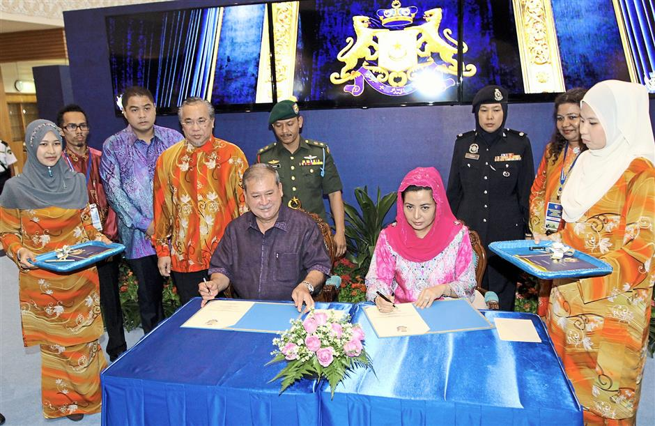 First visitors: Johor Ruler Sultan Ibrahim and Permaisuri Johor Raja Zarith Sofiah signing the attendance book at the entrance of the exhibition in honour of his coronation. — Photos by LIM CHENG KIAT