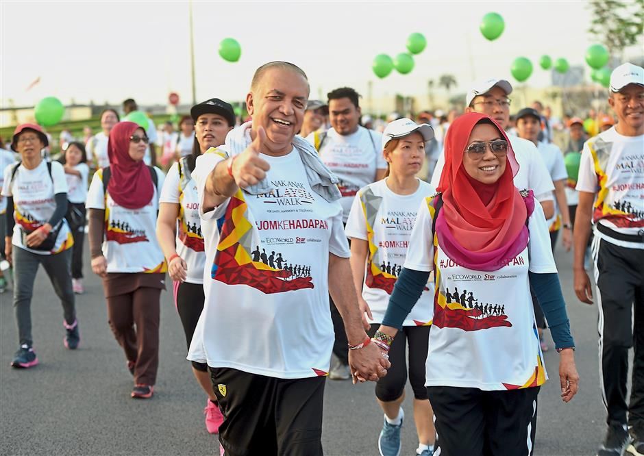 Mydin Mohamed Holdings Bhd managing director Datuk Dr Ameer Ali Mydin (left) with his wife and Mydin director Datin Dr Siti Hawa walking with participants.