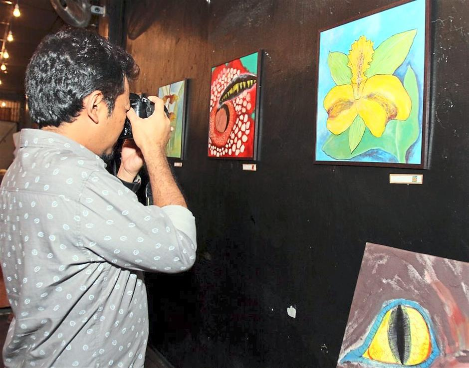 A visitor taking pictures of the Puteri Pakma 2 art exhibition.