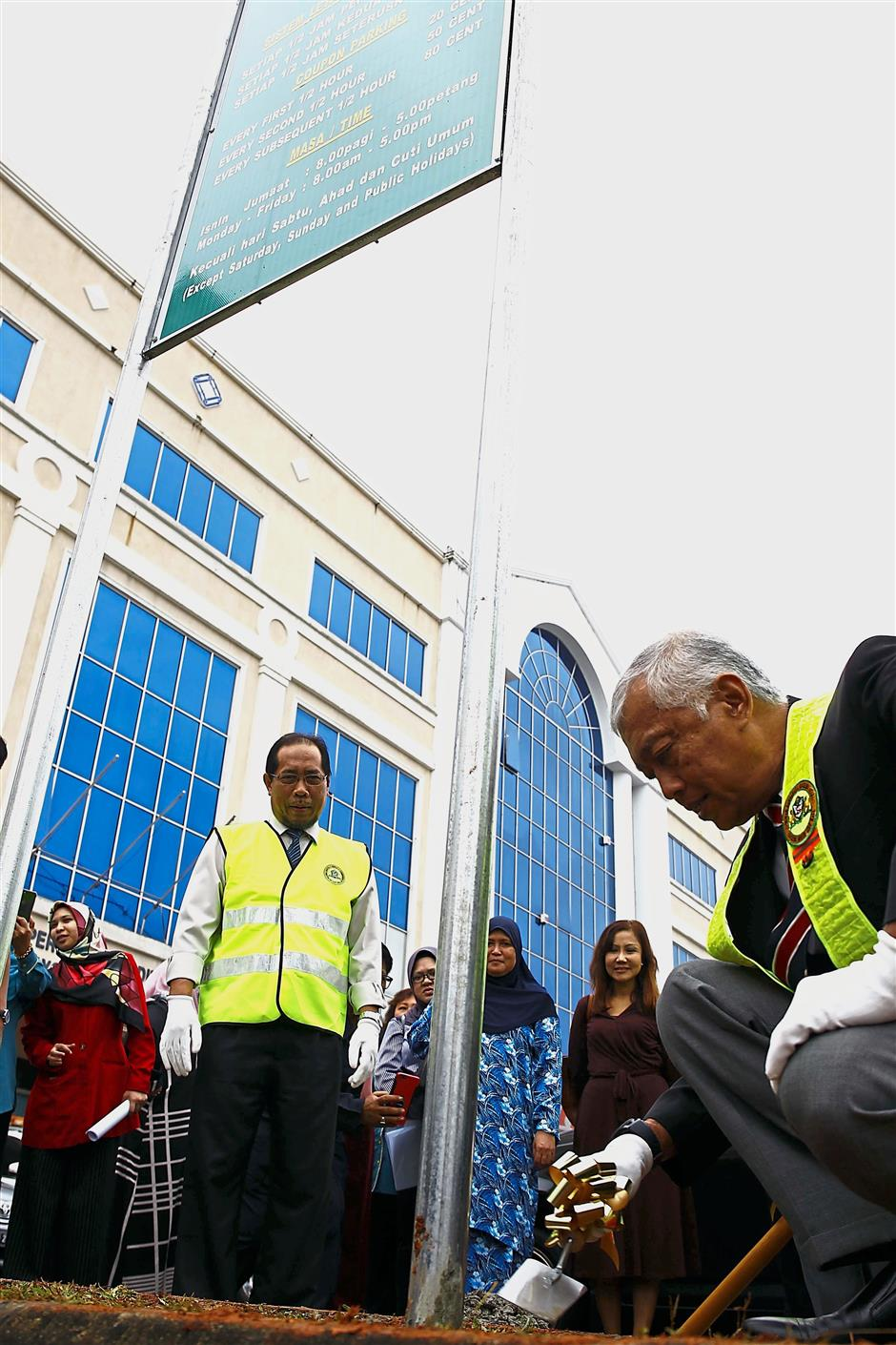 (Below) Abang Wahap leveling concrete at the base of a signboard with information about parking rates at a newly-gazetted coupon parking area at Jalan Kulas. —Photos: ZULAZHAR SHEBLEE/The Star