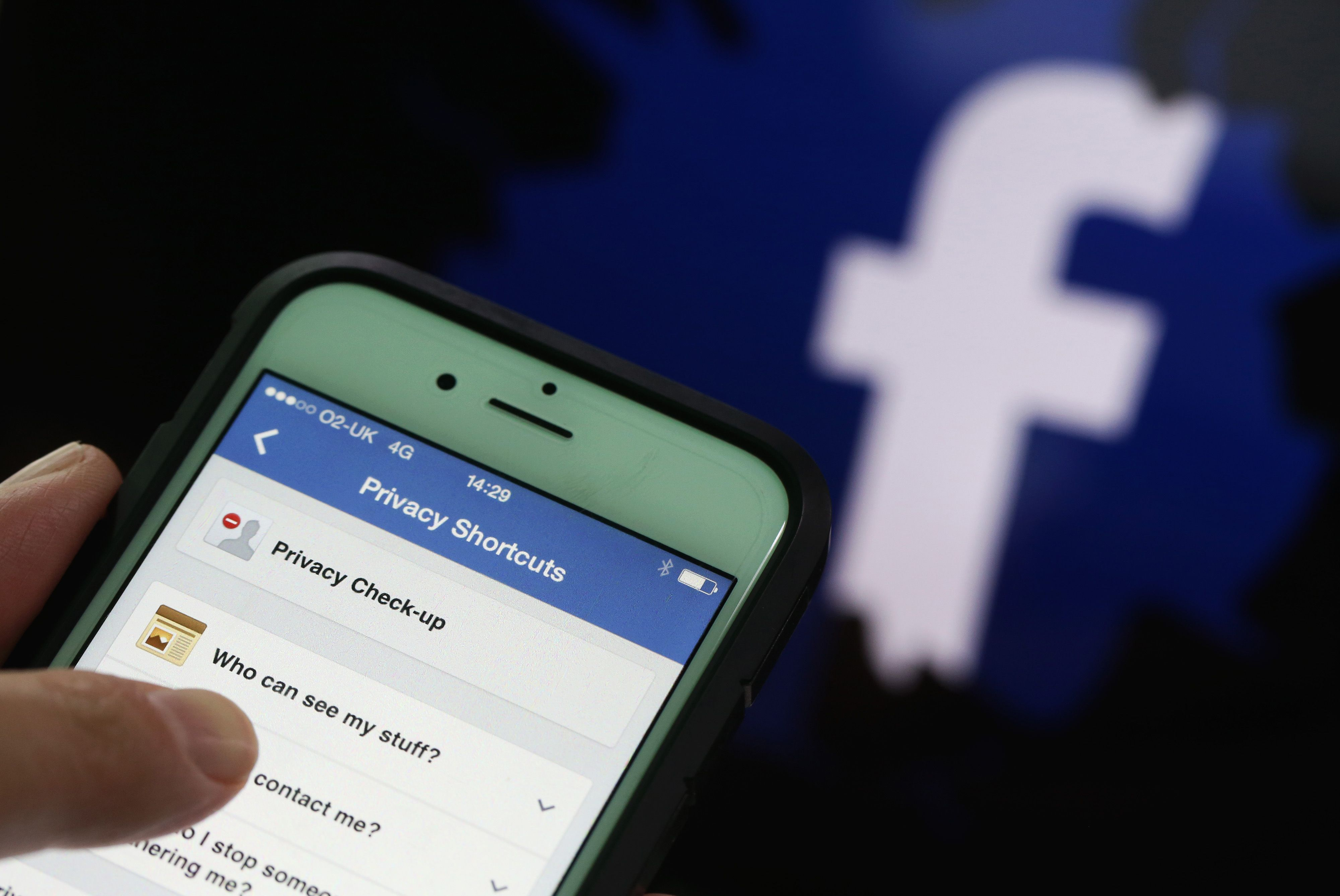 Privacy setting shortcuts are displayed on Apple Inc. iPhone smartphone screen as a FaceBook Inc. logo is seen in this arranged photograph taken in London, U.K., on Friday, May, 15, 2015. Facebook reached a deal with New York Times Co. and eight other media outlets to post stories directly to the social networku00d5s mobile news feeds, as publishers strive for new ways to expand their reach. Photographer: Chris Ratcliffe/Bloomberg