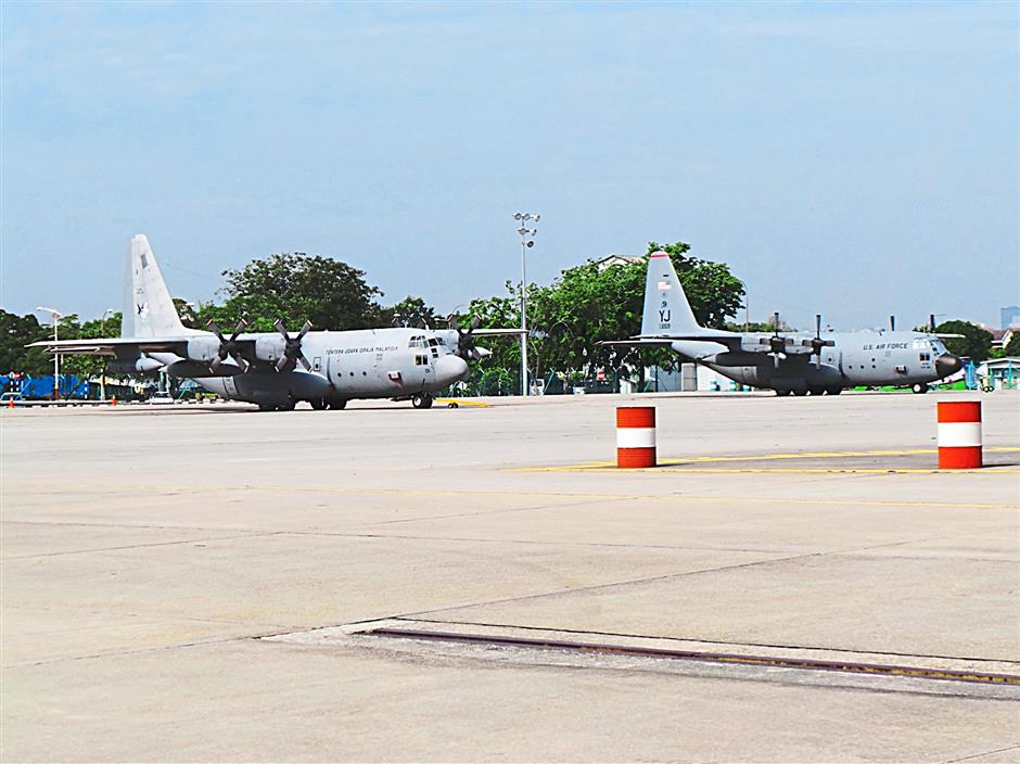 An RMAF C-130 Hercules and a USAF C-130 Hercules parked side by side at RMAF Subang.
