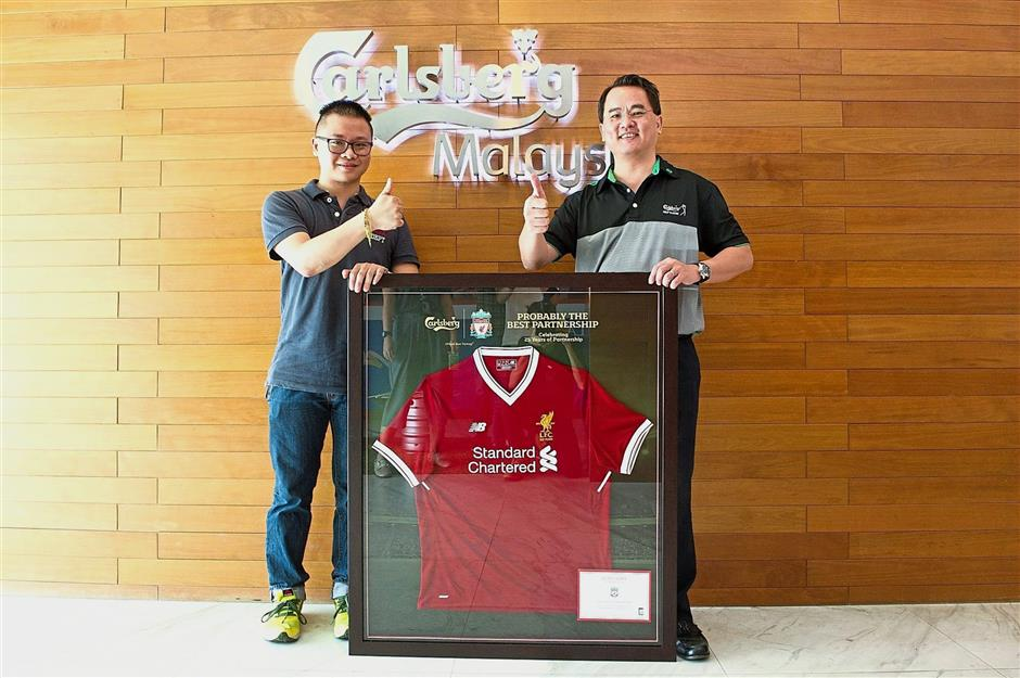 Carlsberg Malaysia marketing director Charles Wong presenting the exclusive limited-edition Liverpool FC jersey to Tan.