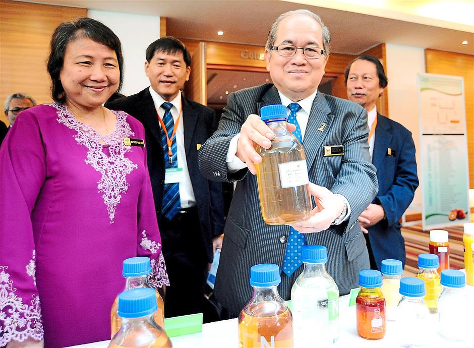 Plantation Industries and Commodities Minister Datuk Seri Douglas Uggah Embas (right) showing the many palm oil products by Malaysia at the Palm Oil Milling, Refining, Environment and Quality 2014 seminar, With him is Malaysian Palm Oil Board director-general Datuk Dr Choo Yuen May (left).