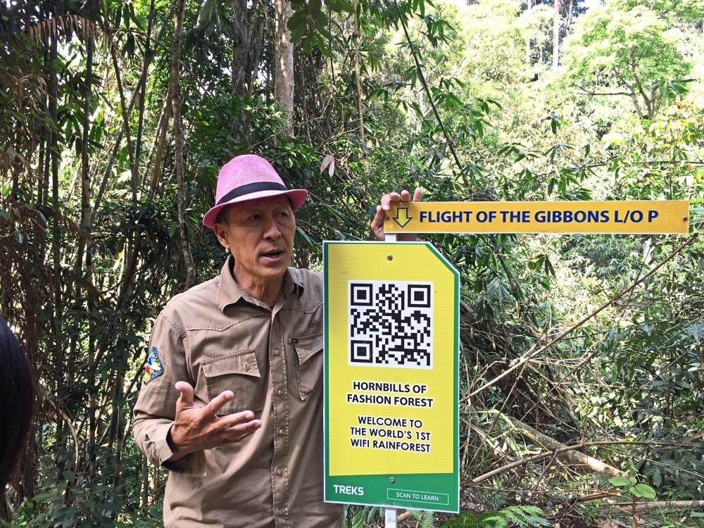 Chan showing what visitors can do and learn with the QR codes placed inside the forest.