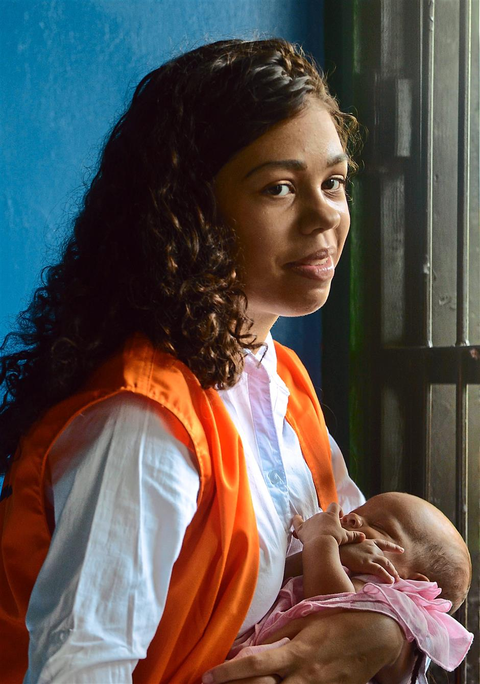 Uncertain future: Mack carrying her young baby inside a holding cell. She was jailed 10 years for assisting in her mother's murder. — AFP