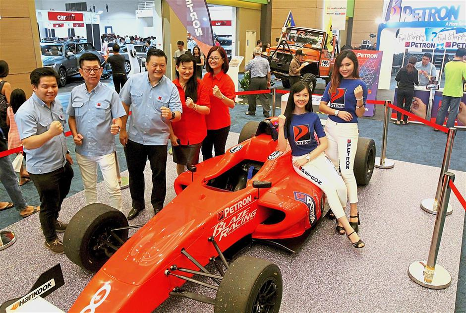 (From left) Petron Malaysia brand performance analyst Ho Wai Khin, lubricants and specialties manager (commercial business) Gary Cheah, marketing manager Danny Chen Heng Siong, Star Media Group Bhd chief content officer Esther Ng and chief revenue officer Lydia Wang with a Formula 4 race car showcased by Petron Malaysia at the event.
