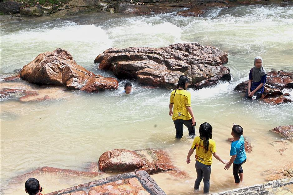 A file image of children playing in a stream. Fire and Rescue Department officials say people going to such areas should always check on weather conditions first and always keep an eye on youngsters.