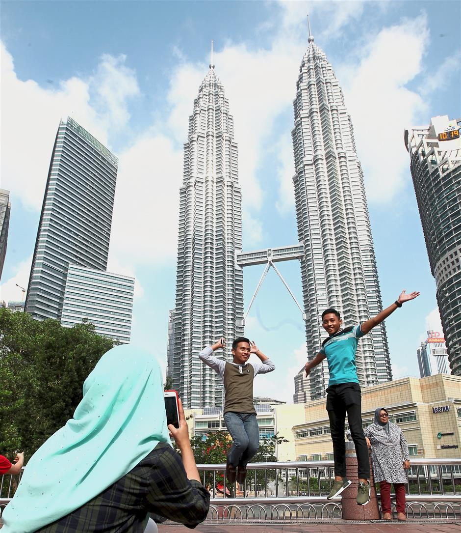 Ahmad Lukman (right) and his brother Abdul Aziz posing for photos in front of the Petronas Twin Towers.