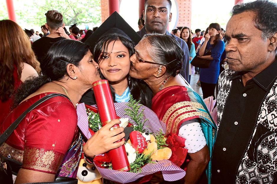 Double the love: E. Rajeswary being kissed on both cheeks by her family members after receiving her scroll during the university's 20th convocation ceremony at its Perak campus in Kampar.