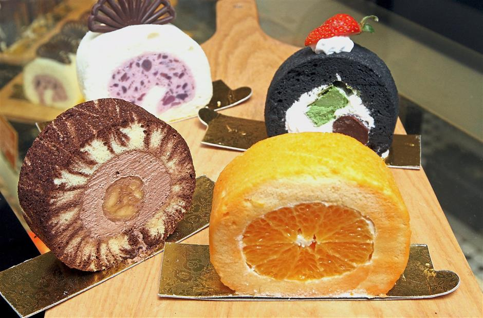 A variety of Swiss rolls with fruit in the middle.