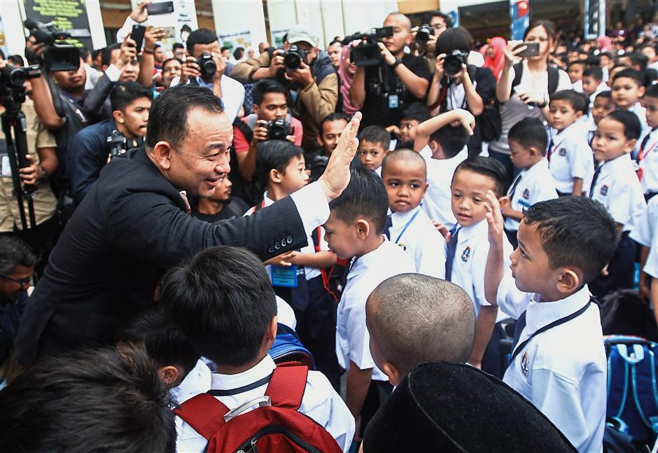 High-five: Dr Maszlee greeting Year One pupils during a visit to SK Putrajaya Presint 14(1).