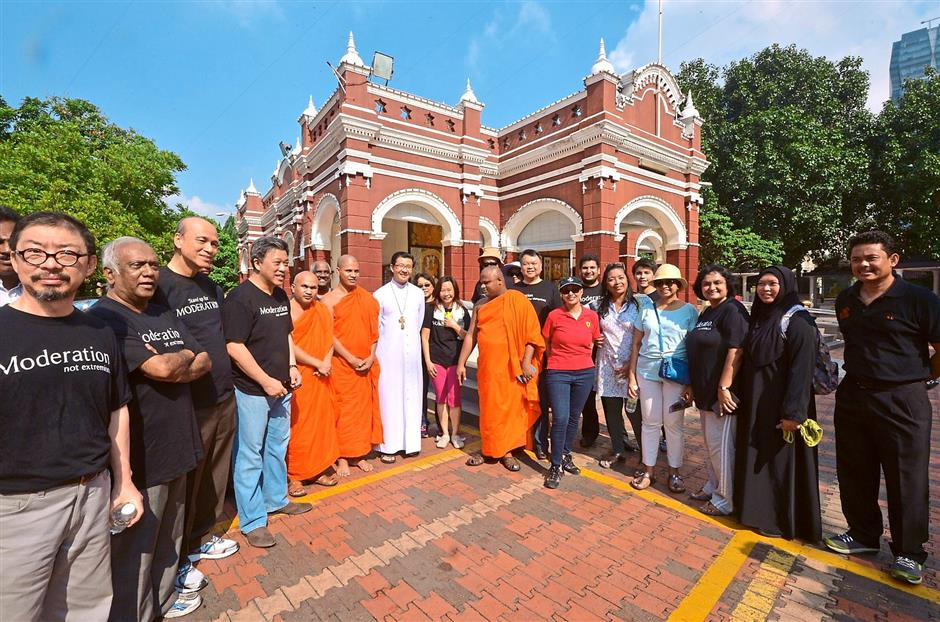 Together as one: The group led by Wong (fourth from left) are seen with Rev Leow (in white robes) and monks in front of the Buddhist Maha Vihara temple in Brickfields.