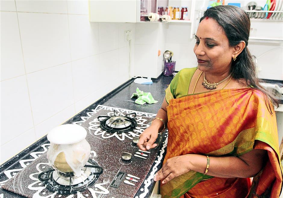 Boiling over: Geetha showing how ponggal is prepared. The name of the special dish literally means boiling over, signifying the festival to give thanks for a bountiful harvest.