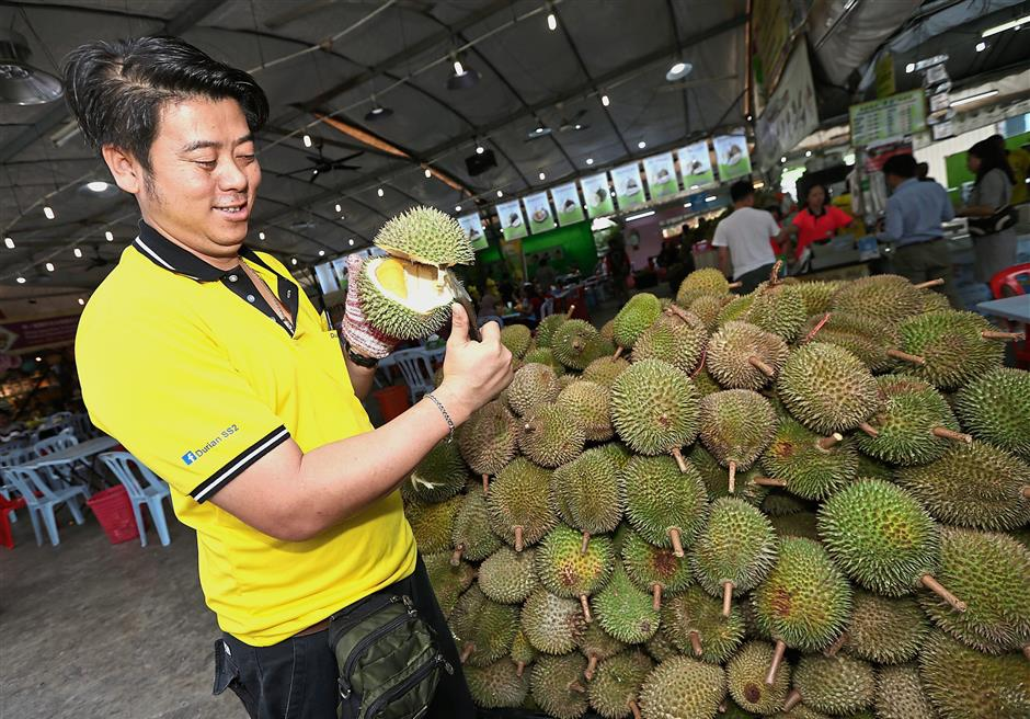 Durian SS Two (1988) Sdn Bhd owner Cheah Kin Wai holding up a fruit at his stall. — Photos: AZHAR MAHFOF and IZZRAFIQ ALIAS/The Star