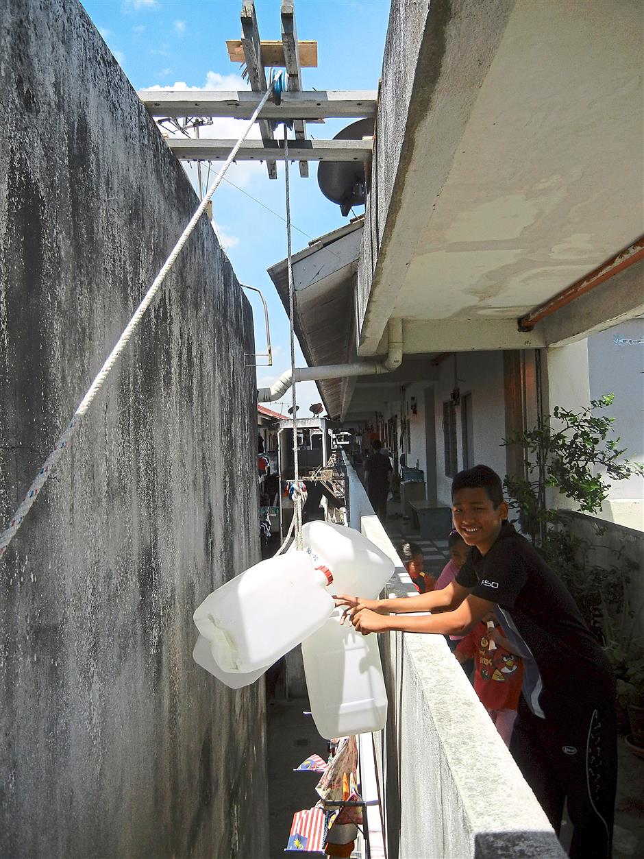 A residents in Taman Impian Ehsan, Balakong, using a pulley to transport water.— Filepic