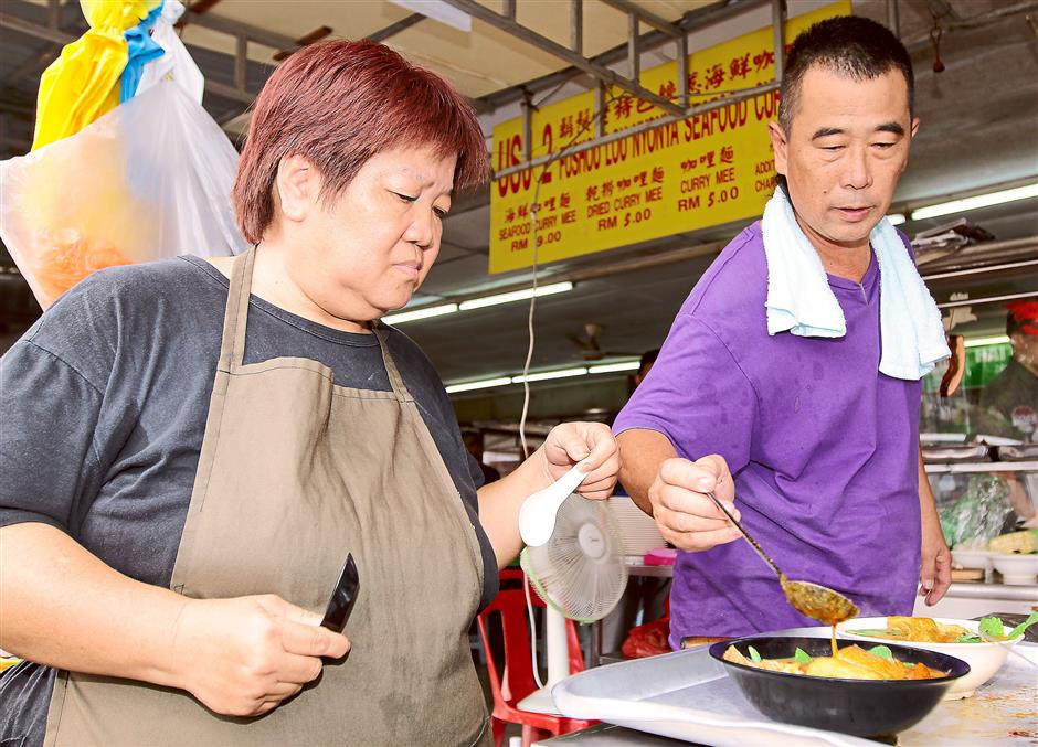Ready to serve: Ipoh-born Kuing Ket Far and his wife Lee Kam Foong putting together the Nyonya-styled curry laksa at the Foushou Lou Nyonya Seafood Curry Stall.