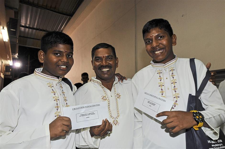 Hard work pays off: Ananthan (middle) with his sons Thanes (right) and Puvanehsan (left) who received excellence awards for the PT3 and UPSR examinations at the Arulmigu Maha Mariamman Devasthanam Temple.
