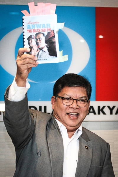 The book in question: Johari holding up the book titled 'Mengapa Anwar Tak Boleh Jadi PM' written by Yahaya at the PKR headquarters.