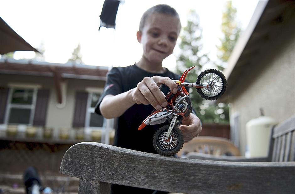 Colton Nelson plays with his toy motorcycle in his backyard. He has a rare autoimmune disease called Job's syndrome, which requires he be injected with gamma globulin once every 21 days to build antibodies that he does not naturally have. — MCT