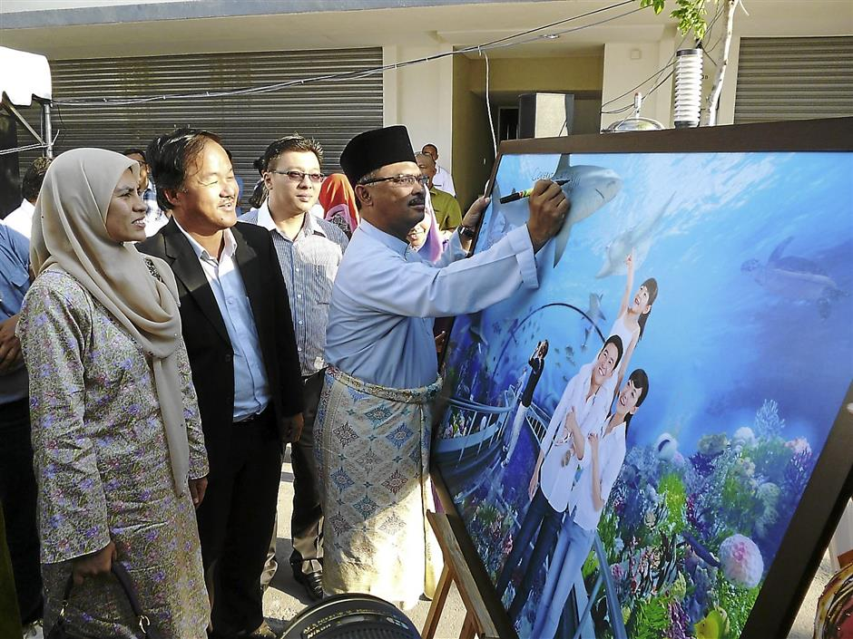 Malacca Chief Minister Datuk Wira Ir Idris Haron  signing the Malacca Oceanarium Complex posters during the Groundbreaking Ceremony at Bunga Raya Pantai, Melaka.