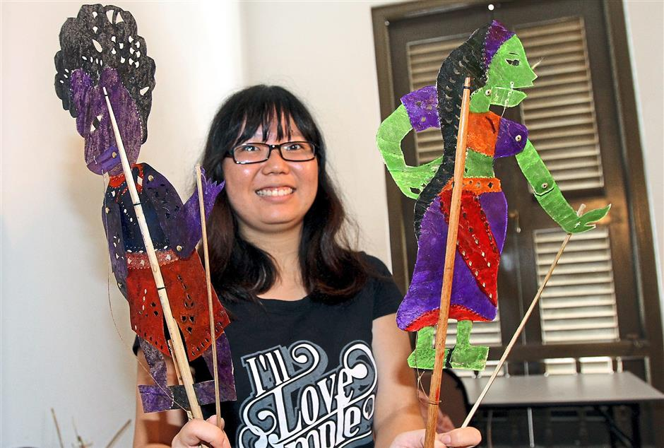Xxx: One of the performers showing the puppets used in Wayang Chulia.