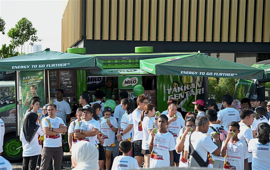 Participants enjoying cold cups of Milo after the walk.