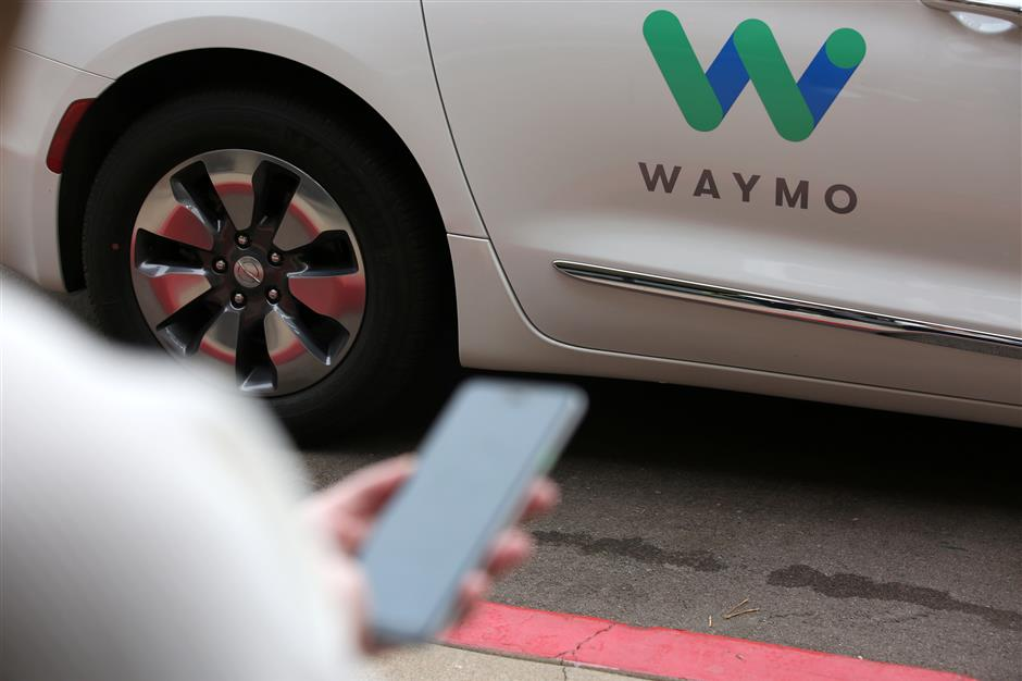A Waymo employee hails a ride on their phone during a demonstration in Chandler, Arizona, November 29, 2018. Picture taken November 29, 2018. REUTERS/Caitlin Ou2019Hara