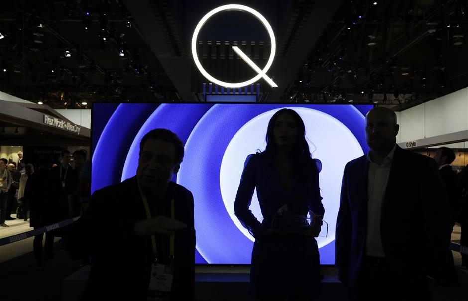 FILE- In this Jan. 6, 2017, file photo attendees stand in front of a QLED TV at the Samsung booth during CES International in Las Vegas.  Critics have been on the case of one of the tech industryu2019s largest trade shows for not including enough female speakers. That seems to be changing this year at CES, the huge consumer-electronics show in Las Vegas. Last year, CES initially had no female keynote speakers, and drew heavy criticism. This year, activists have given it an award for the gender and racial balance of its speaker lineup. (AP Photo/John Locher, File)