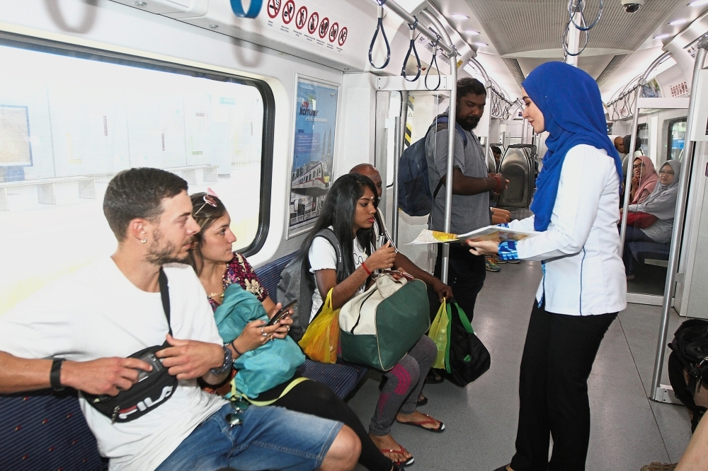 (MAIN PIX) KTM staff handing out brochures on the Thaipusam 2019 Non Stop KTM Komuter Service to Batu Caves to passengers. AZLINA ABDULLAH/The Star