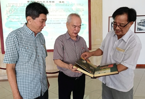 Tiong (right) looking through the book donated by Wong (centre) while Goh looks on.