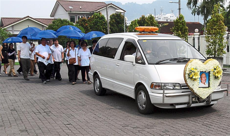 Tan Jin Eong family members walking behind the hearse during the funeral service.