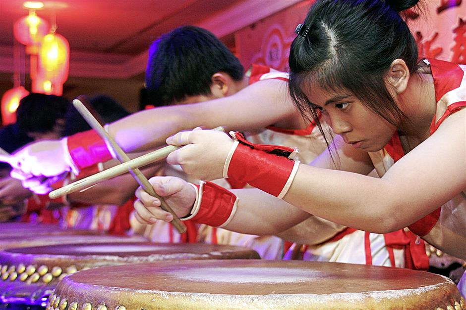 Hakka youngsters playing the drum during a performance at the Five Hakka Clans Associations Chinese New Year celebration dinner here on Monday.
