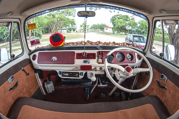 Soft brown leather seats and red panelling on the dashboard of the camper van.