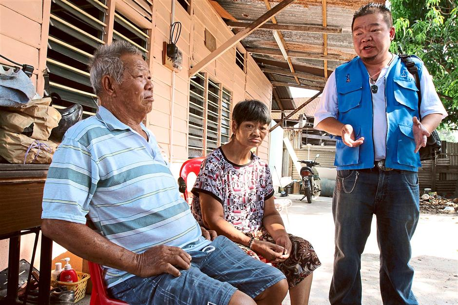 Seeking help: Lee (right) speaking to Chang at the odd-job worker's home. Lee said the couple's situation was pitiful and urged the public to help in any way they can.
