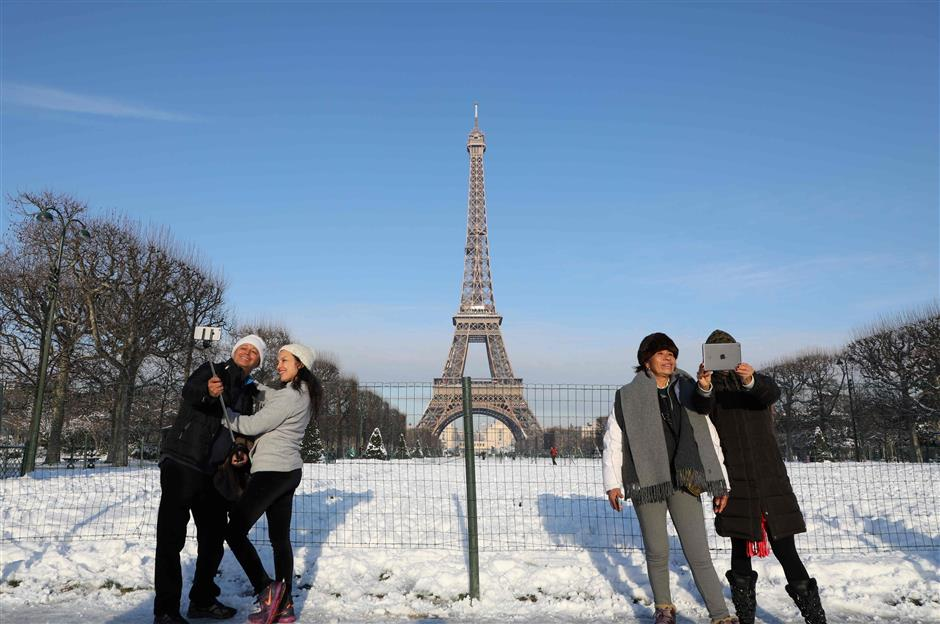 Couples stand in the snow as they pose for \'selfies\' in front of The Eiffel Tower in Paris on February 8, 2018.  / AFP PHOTO / ludovic MARIN