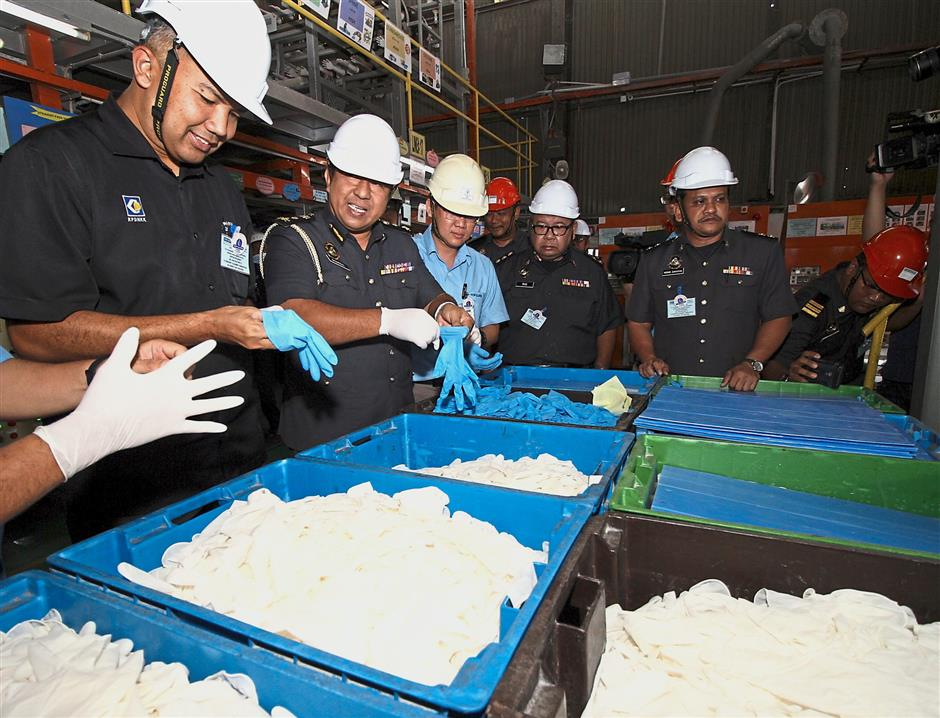 Perak Domestic Trade, Co-operatives and Consumerism director Saifullizan Kamarul Zaman (left) and Perak Domestic Trade, Co-operatives and Consumerism enforcement chief Shamsul Nizam Khalil (second from left) along with other officers trying out rubber gloves during a check at Top Glove factory in Ipoh..