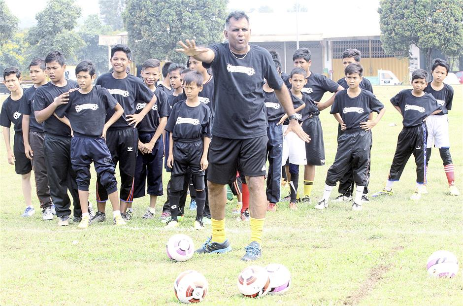 Stop there: Former national defender Gunalan giving instructions to the youngsters during the clinic.