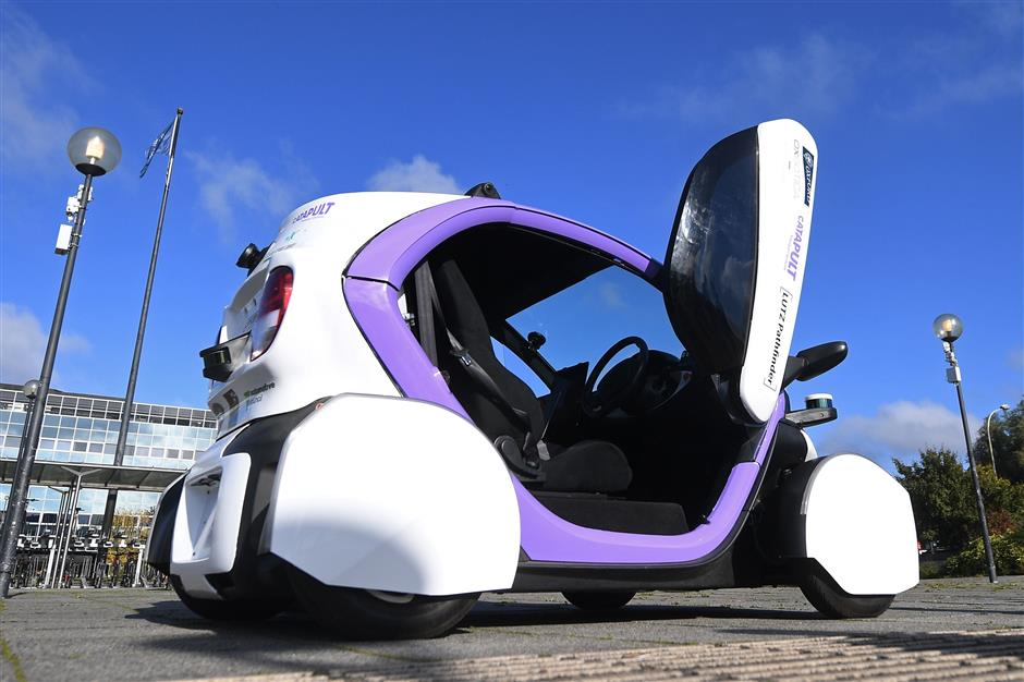 (FILES) This file photo taken on October 11, 2016 shows an autonomous self-driving vehicle, pictured during a media event in Milton Keynes, north of London, on October 11, 2016. A driverless, electric car is only a swipe away in the cities of the future, where pollution clampdowns and rapid advances in technology will transform the way we travel, despite lagging infrastructure. As more and more countries announce a phasing-out of pure petrol and diesel cars, early versions of tomorrow\'s models are already on the streets: hybrid cars, fully electric motors and vehicles that can partially drive themselves.  / AFP PHOTO / JUSTIN TALLIS