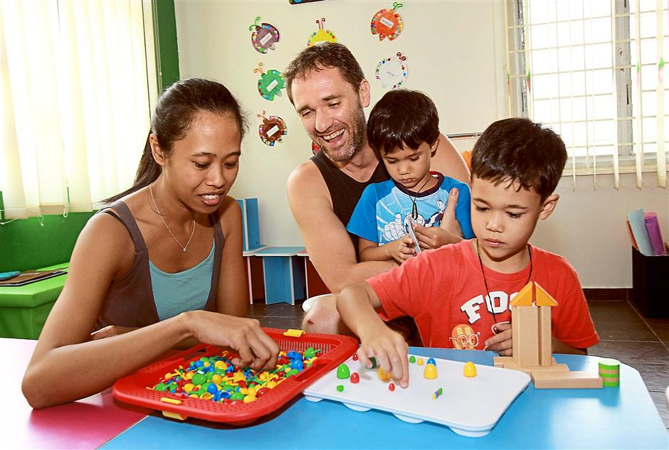Michael Wilson, 37, and wife Amirah Mohamad, 33 with their sons Matai, 5, and Kae, 4, at KinderKaizen, an enrichment centre where children are encouraged to use play to support their learning and development.
