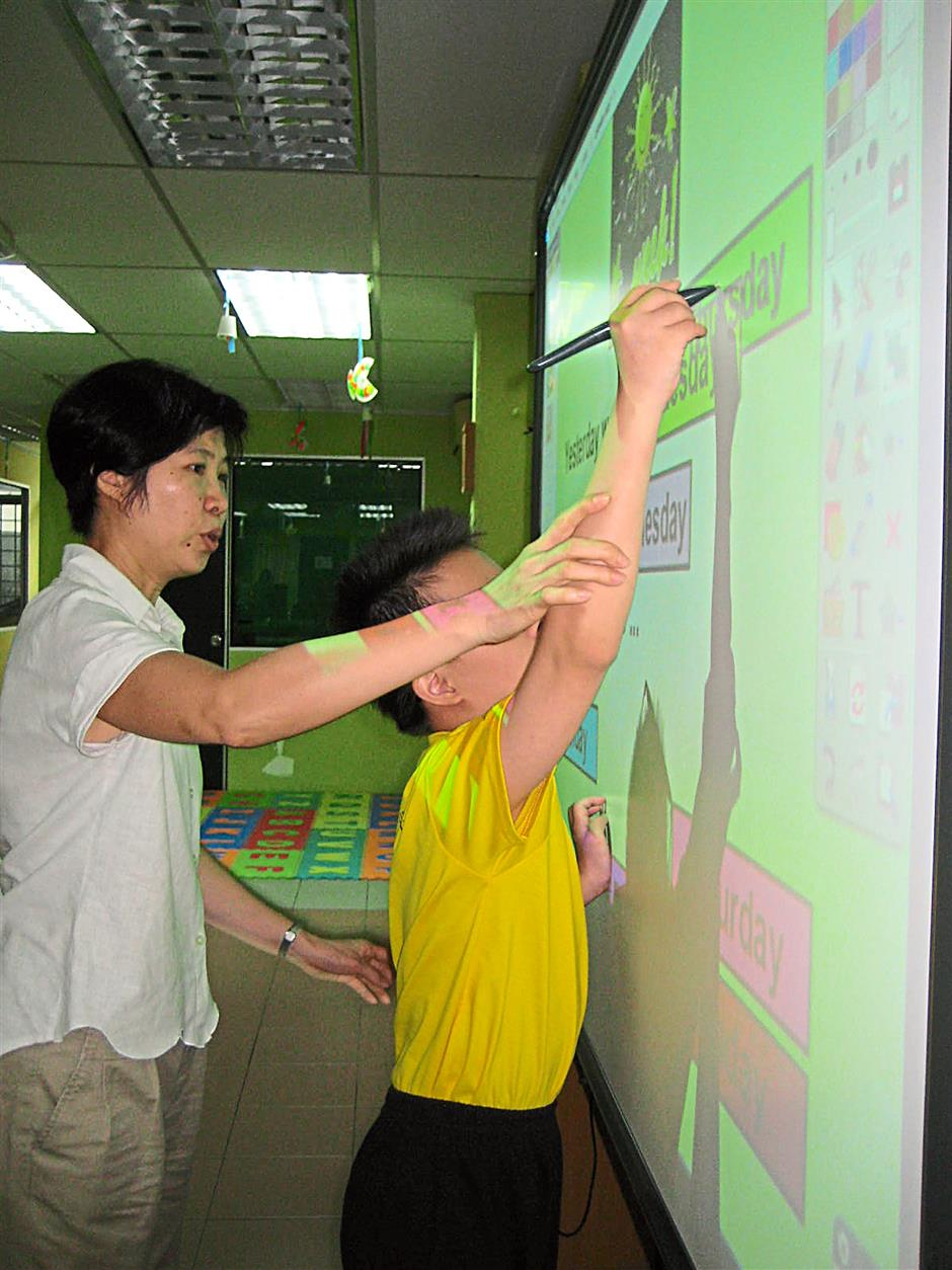 Let's write: A teacher helping a pupil write out a missing letter on the board.