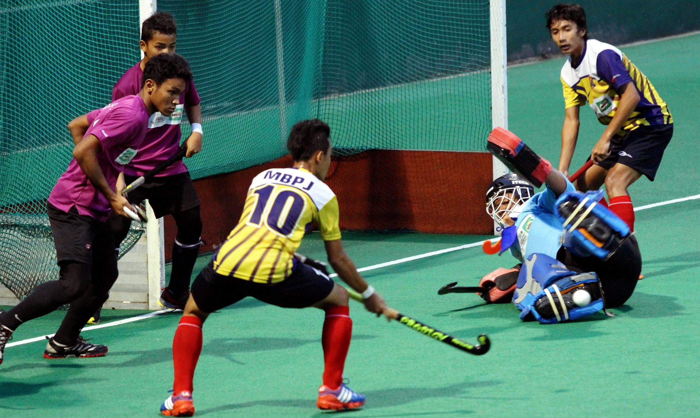 An MBPJ player (in yellow) attempting a field goal against Malacca High School in their Malaysian Junior Hockey League Div 1 match in Kuala Lumpur on Sunday. - SHAARI CHEMAT/The Star