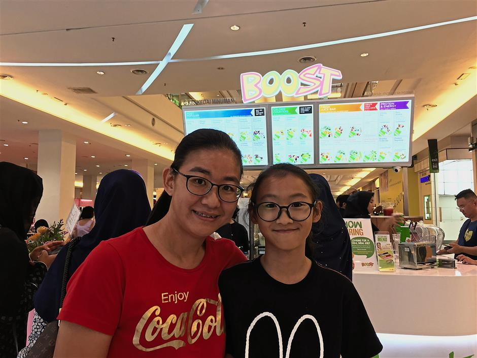 Khong (in red T-shirt) and her daughter enjoyed the special offer at the fruit juice outlet.