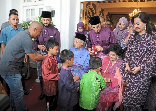 (Above) Cheng (second right) and Kedah Chinese Assembly Hall committee members enjoying their meal. (Right pic) Mukhriz (in purple), accompanied by his wife Norzieta (next to him) and two children (in blue), distributing duit Raya to children at his Hari Raya open house.