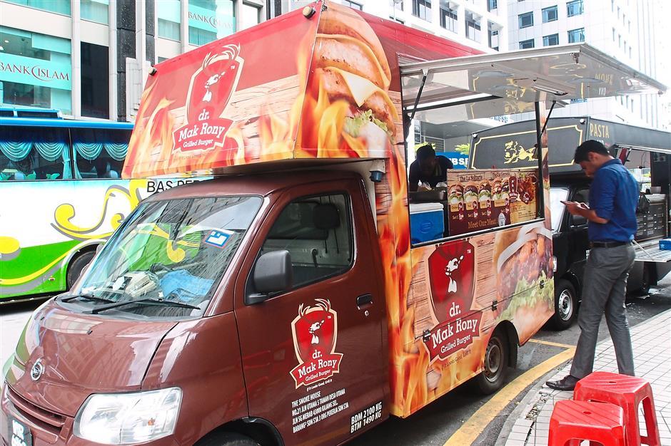 2. Dr Mak RonyA customer waits for his grilled burger at the Dr Mak Rony food truck along Jalan Dungun, Damansara Heights. For MOB Top 10 story on 10 trending food trucks.