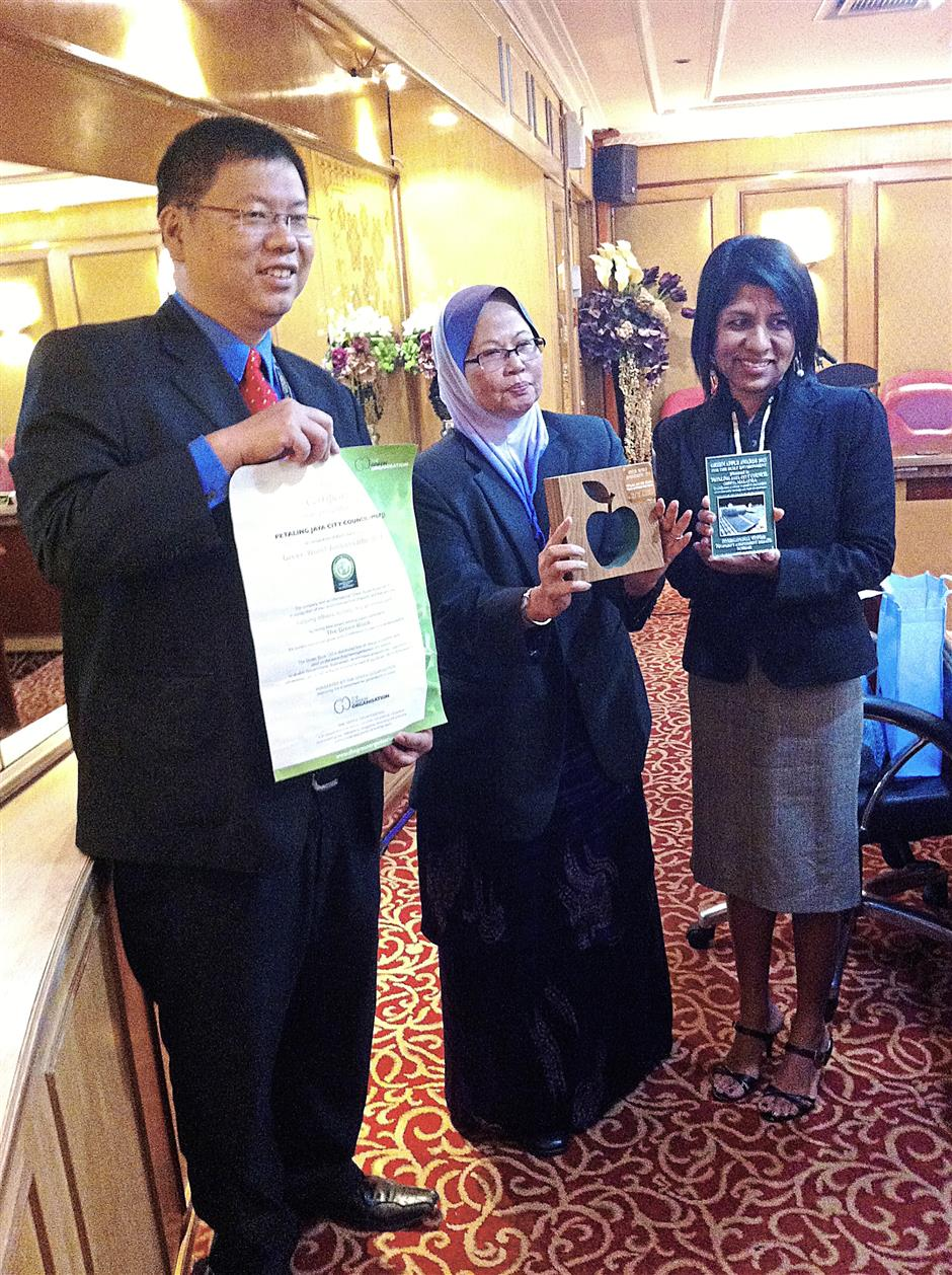 Petaling Jaya City Council (MBPJ) mayor Datin Paduka Alinah Ahmad together with MBPJ's One-Stop Centre unit head Lee Lih Shyan and former councillor Cynthia Gabriel showing off the Green Apple award given to them by the Green Organisation for their Green Rebate Scheme.